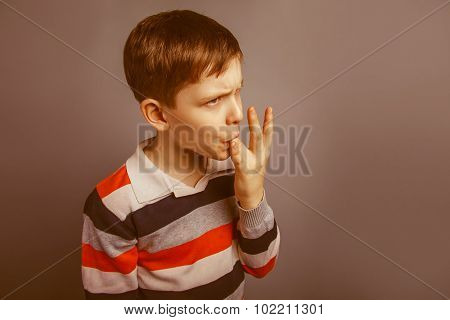 European-looking boy  of ten  years licks his finger on a gray b