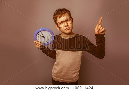 European-looking boy of ten years in glasses holding a wall cloc