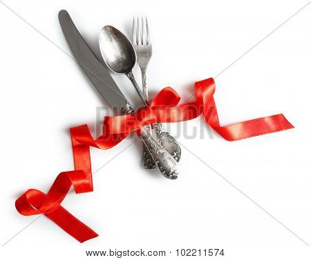 Cutlery tied with ribbon on light background