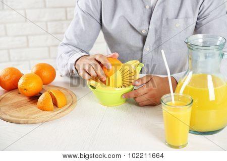 Young man using citrus-fruit squeezer, preparing orange juice