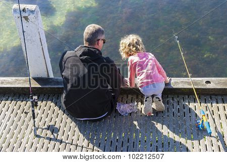 View Of Father And Daughter Fishing