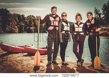 Group of people wearing life jackets near kayaks on a beach