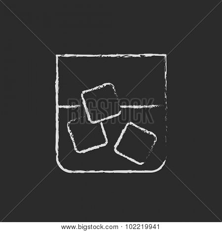 Glass of water with ice hand drawn in chalk on a blackboard vector white icon isolated on a black background.