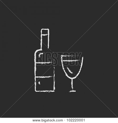 A bottle and a glass hand drawn in chalk on a blackboard vector white icon isolated on a black background.