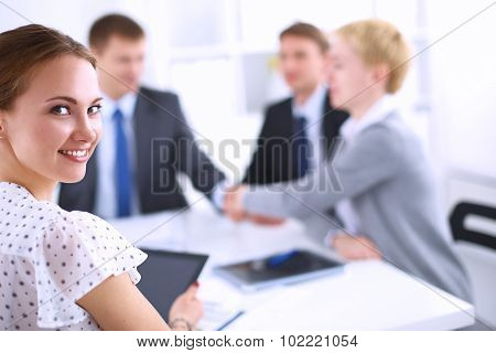View of a team of businesspeople  shaking hands with a businesswoman in front of them
