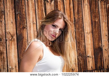 Woman posing with wooden planks in a background
