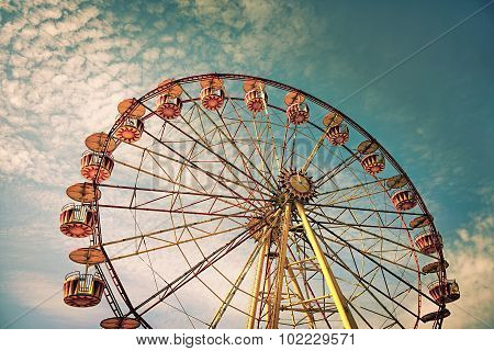 Yellow Ferris Wheel Against A Blue Sky In Vintage Style
