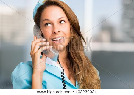 Portrait of a smiling stewardess talking on the phone