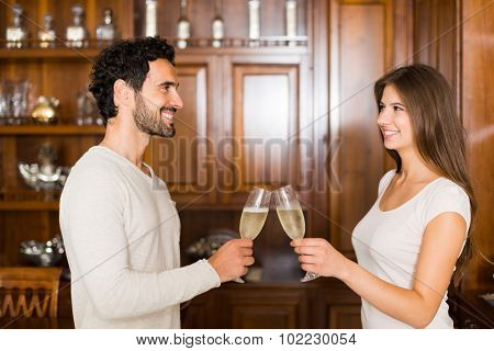Couple toasting champagne flutes in their apartment