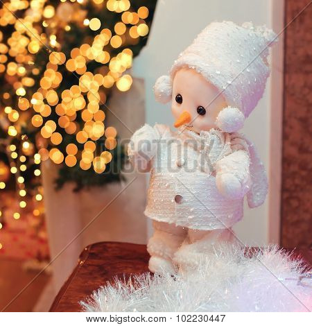 Christmas Decoration, Miniature Snowman Over Bright Blurred Bokeh Of Garland