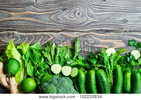 Fresh green vegetables on vintage wooden background. Detox, diet or healthy food concept