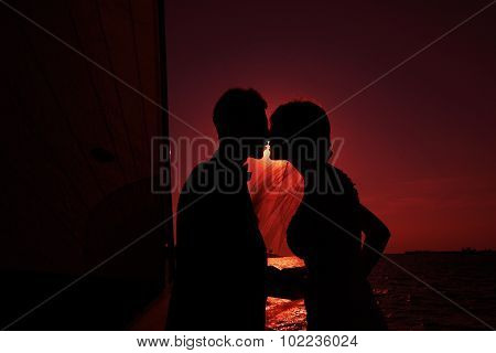 newlyweds kiss against the setting sun