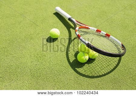 Tennis racket and balls on the court grass
