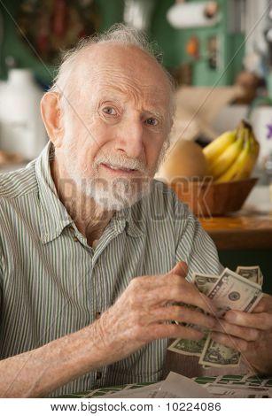 Senior Man At Home Counting Money