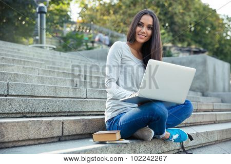 Portrait of a cheerful female student sitting on the city stairs and using laptop computer outdoors