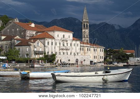 PERAST, MONTENEGRO - YULY 13: scene of marina with row boats and old stone buildings of Perast village against a dramatic sky. Shot in 2014