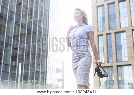 Low angle view of confident businesswoman holding high heels while standing outside office buildings