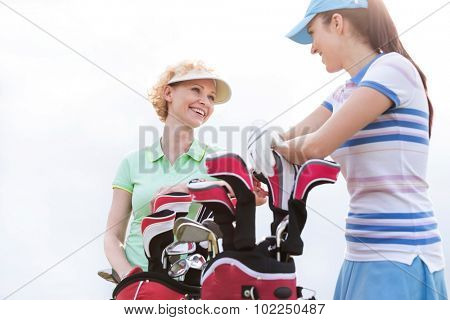 Low angle view of happy female golfers talking against clear sky