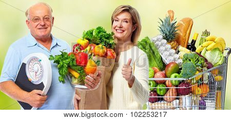 Elderly couple with scales and vegetables over green background.