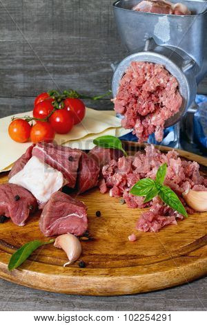 Beef, Onion, Raw Meat, Lasagna Sheets, Cherry Tomatoes And Grinder On A Dark Gray Wooden Table