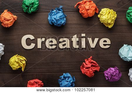word creative and crumpled colorful paper