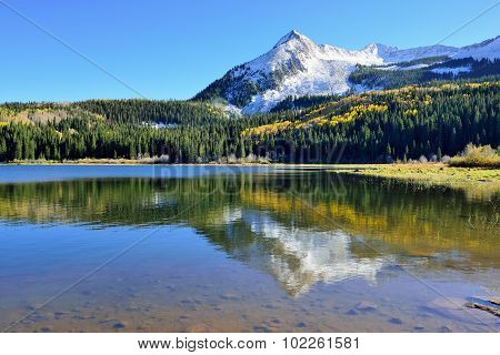 Alpine Scenery Of Yellow And Green Aspen, Snow Covered Mountains And Reflection In The Lake During F