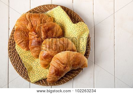 Fresh croissant, on a yellow napkin and wicker basket. Overhead view with space for text.