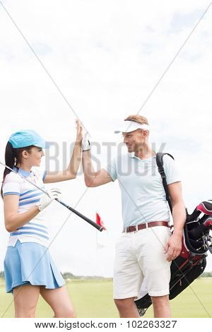 Happy male and female friends giving high-five at golf course