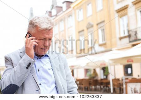 Middle-aged man using mobile phone in city
