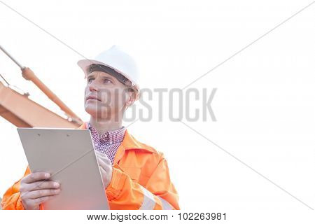 Supervisor looking away while holding clipboard against clear sky