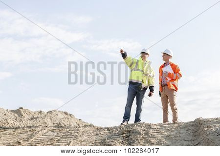 Low angle view of supervisor showing something to colleague at construction site