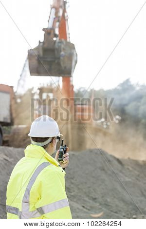Side view of engineer using walkie-talkie at construction site