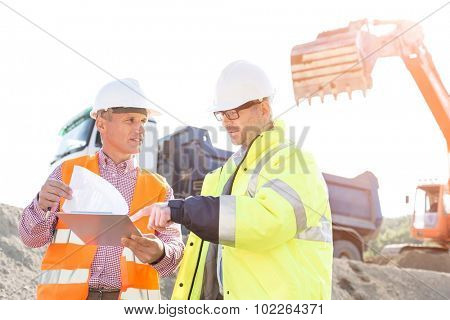 Engineers discussing over documents at construction site