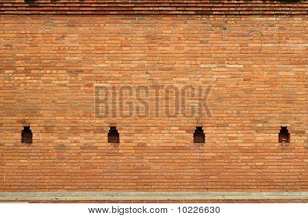 Ancient brick wall.With a hole to see the enemy at war