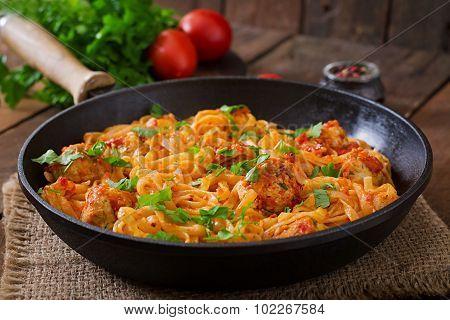 Pasta linguine with meatballs in tomato sauce.