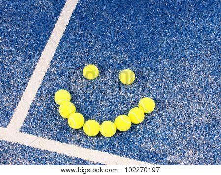 Smiley of Tennis balls on a blue artificial grass court