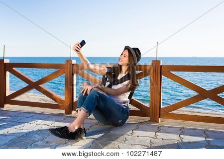 Female hipster taking picture of herself on smart phone strolling on the beach