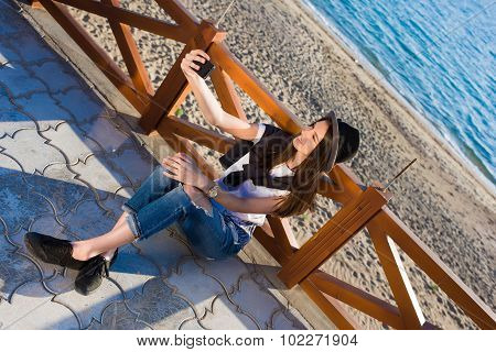 Hipster girl making self portrait with her smart phone digital camera while enjoying summer day