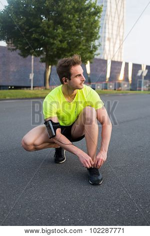 Sportsman with armband on the arm rest after run while listening to music in headphones