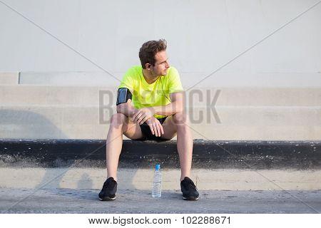 Male runner listen to music in headphones while admiring morning sunrise in summer