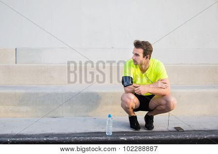 Male runner listen to music in headphones though cell phone and admiring city landscape