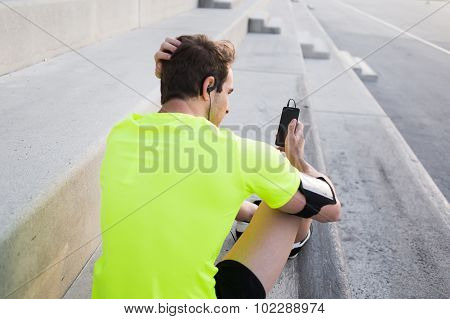 Young sports man with mobile phone in the hand sits on steps taking break between training outside