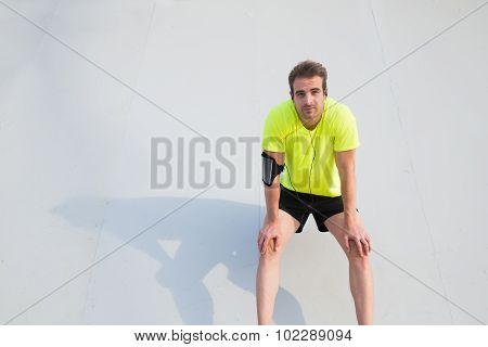 Young sports build man listen to music and rest after active workout outdoors copy space area