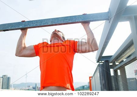 Young muscular build man doing pull ups exercises on horizontal bar outdoors