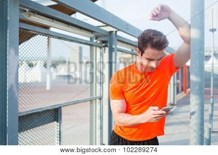 Young caucasian man using smart phone while taking break after active training in the fresh air