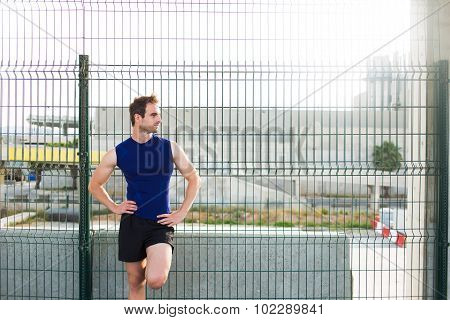 Half length portrait of handsome man with athletic body rest after workout exercise outdoors