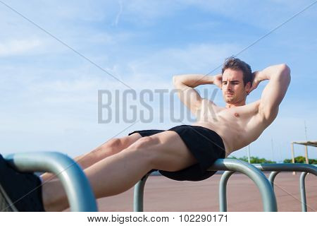 Young athletic man warming up in the fresh air in summer day