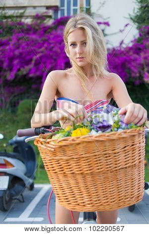 charming hipster girl leaning on her retro bike with a basket of summer flowers resting after riding