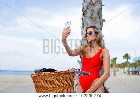 Seductive female in swimwear taking self portrait with smart phone on the beach
