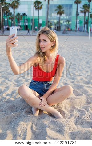 Young beautiful woman taking self picture with smartphone while sitting on the seashore